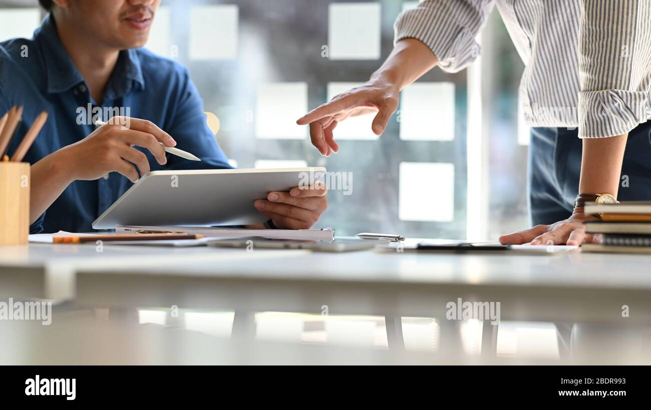 Business development team while discussing/meeting at the modern meeting table with computer tablet and document. Comfortable workplace concept. Stock Photo