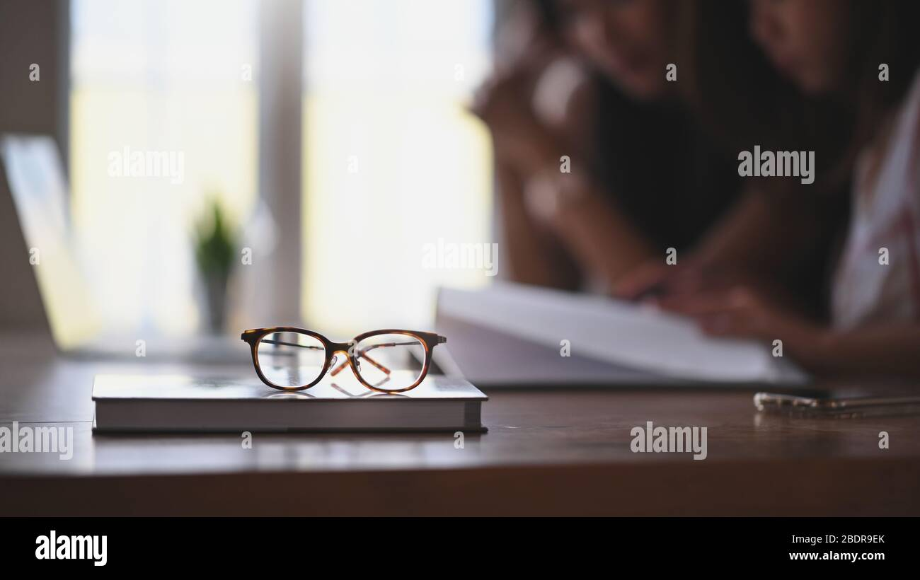 Glasses and book putting together on wooden table with two woman as blurred background. Library/Quiet place for reading book concept. Stock Photo