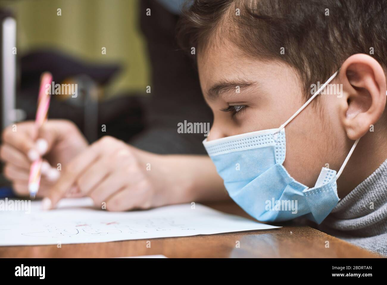 Distance education. Mother helps pre-school kid to do lessons. Education at quarantine time. Protection of Children during the Coronavirus Pandemic Stock Photo