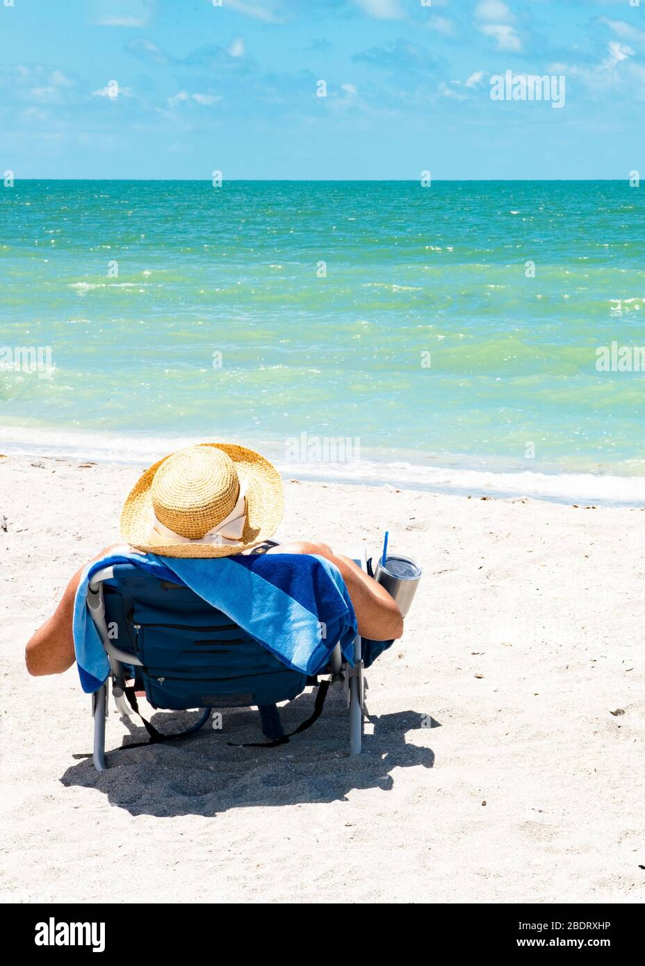 Person Sitting In A Lounge Chair On The Beach Looking Out At The Ocean Person Is Wearing A Hat Person Is Unrecognizable Stock Photo Alamy