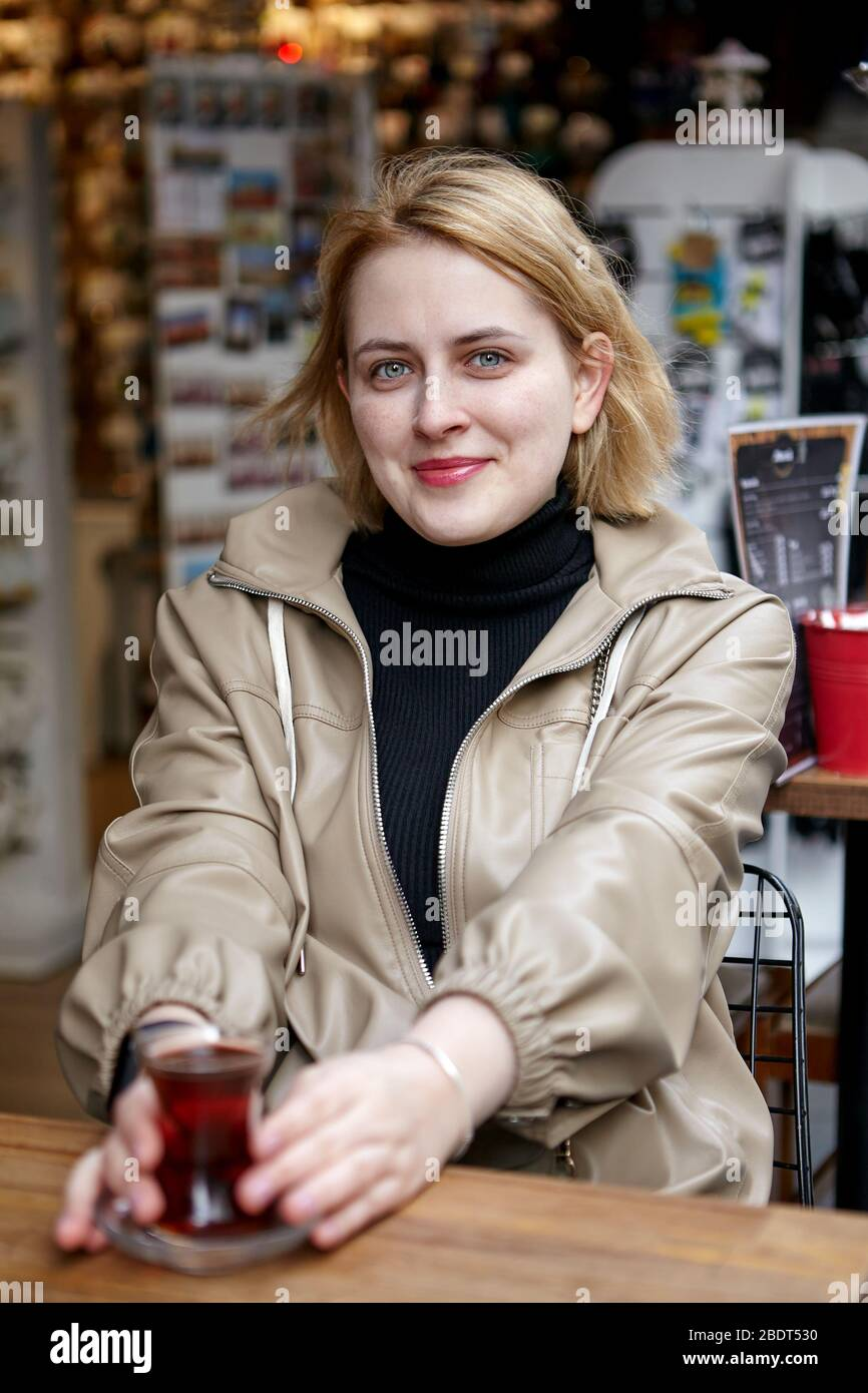 Young pretty white caucasian woman in casual raincoat is sitting in the outside cafe with small cup of Turkish tea in her hands. Stock Photo