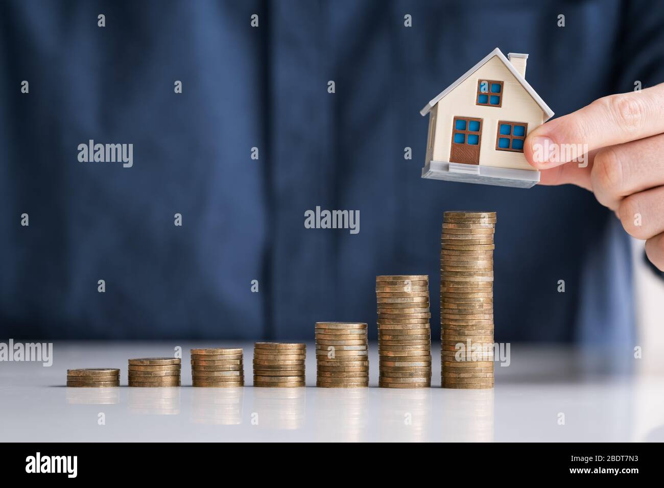 Close-up Of Businessman Hand Arranging House Model On Stacked Coins At Desk Stock Photo