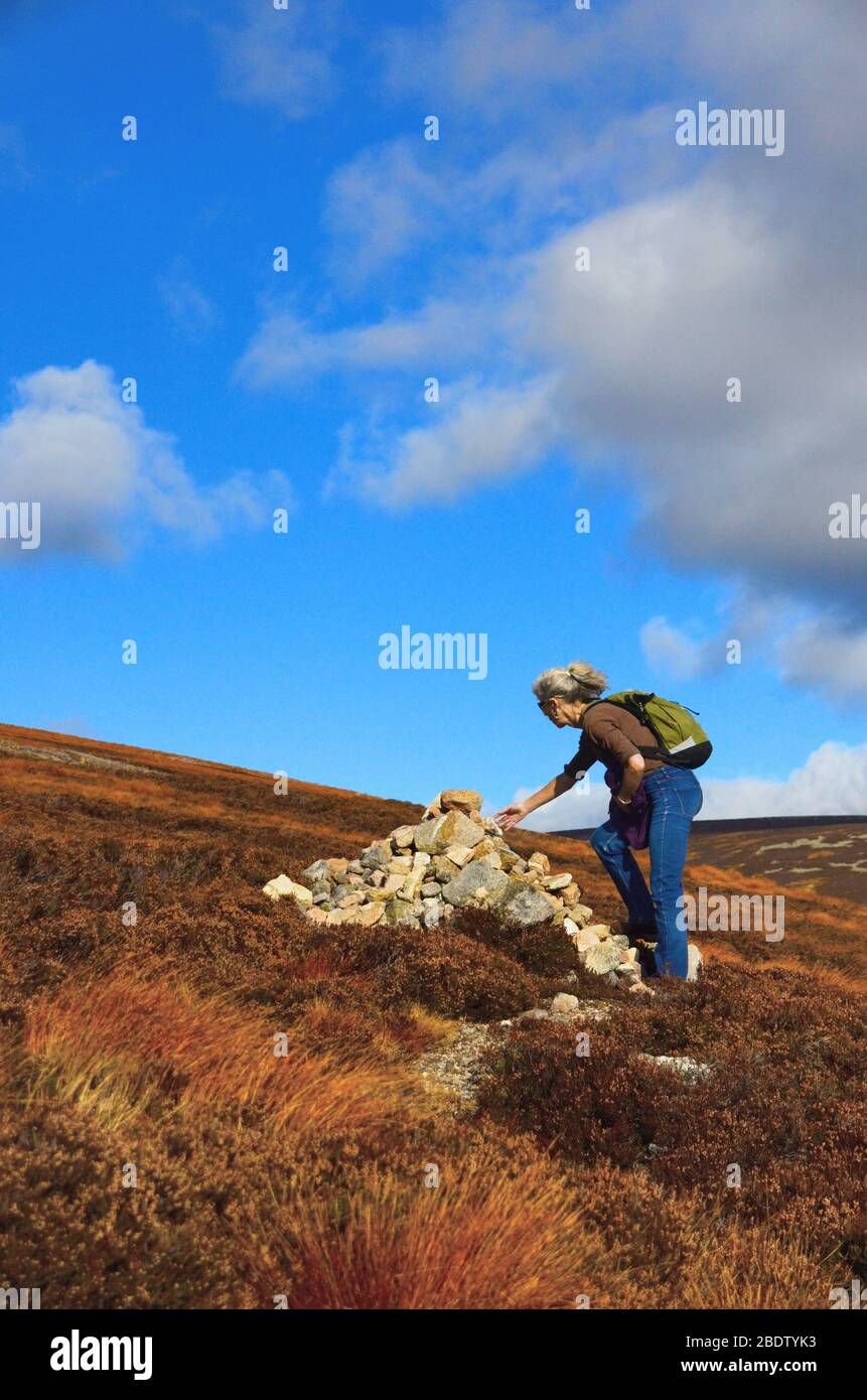 A woman adding a rock to a cairn at the side of a footpath leading to the top of Mount Keen, at glen Esk Stock Photo