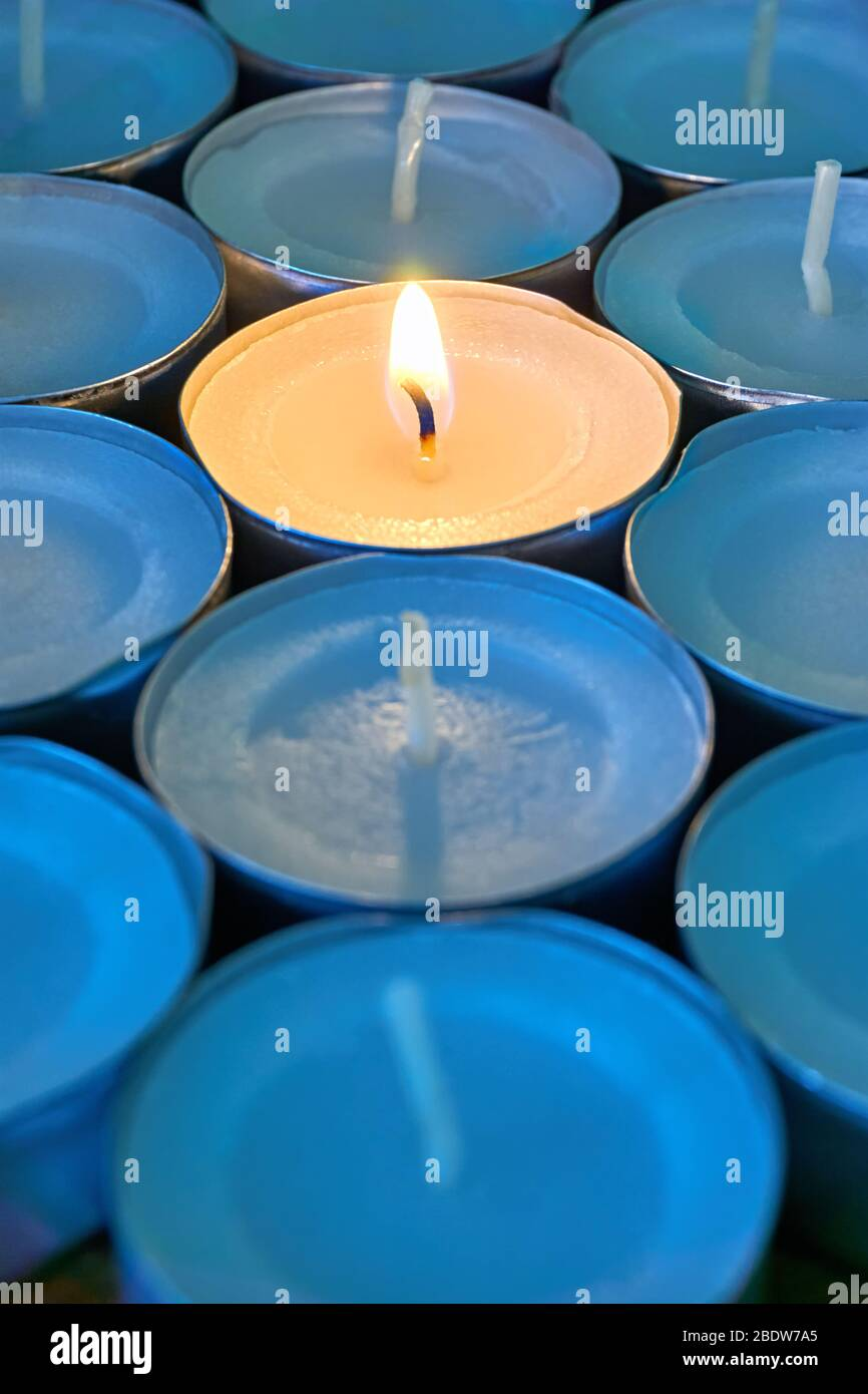 Closeup of tea lights with one being lit. A single warm orange flame between  candles in blue shadow. Christmas, mourning or condolence concept. Stock Photo