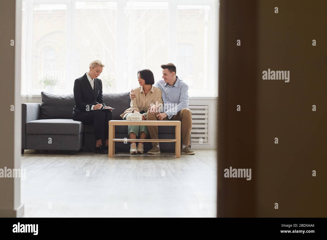 Mature real estate agent in black suit sitting on sofa together with young couple and signing the contract Stock Photo