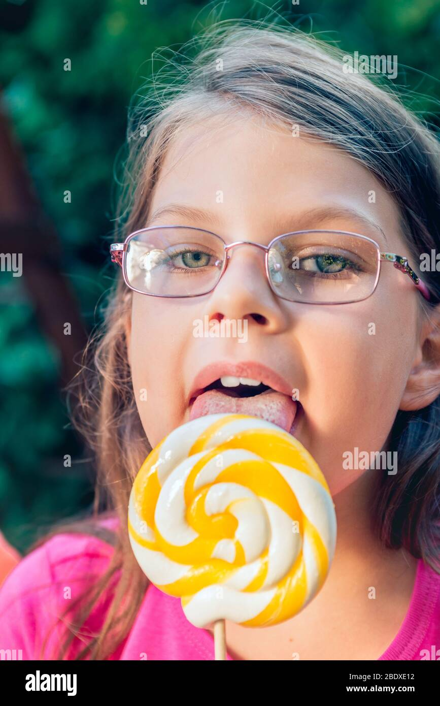 Little girl in glasses licking big lollipop Stock Photo