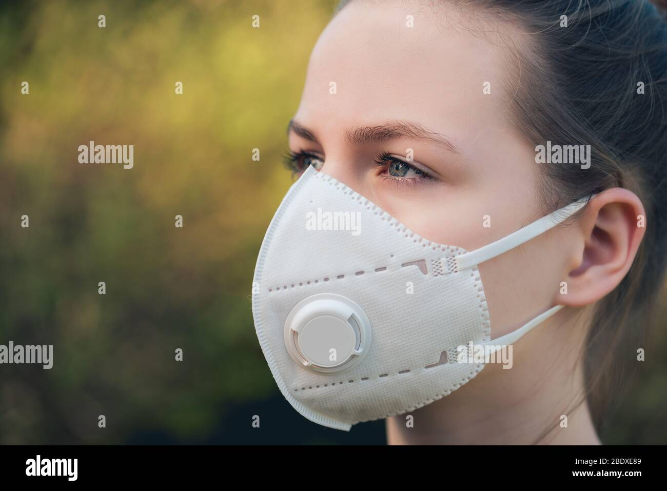young girl with anti-virus anti-smog mask on her face. Wearing hygiene masks reduces the risk of getting COVID-19 disease caused by coronavirus; it al Stock Photo