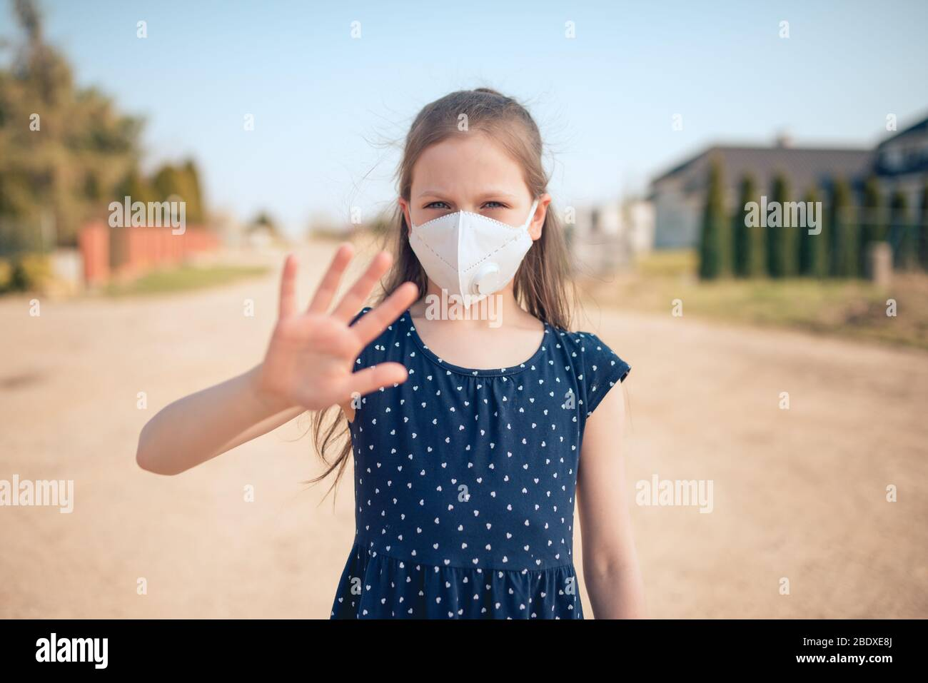 Coronavirus and air pollution concept. Little Caucasian girl wearing face mask for protection and showing stop hand gesture for stoping corona virus o Stock Photo