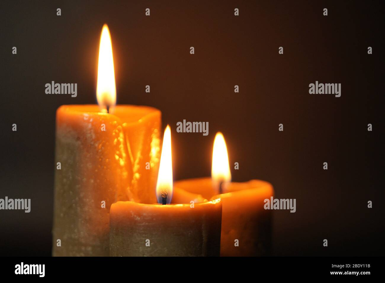 Group of three brown burning candles on a black background close-up. Concept of comfort,romance,mystic,occultism,religion,a symbol of memory.Copy Stock Photo