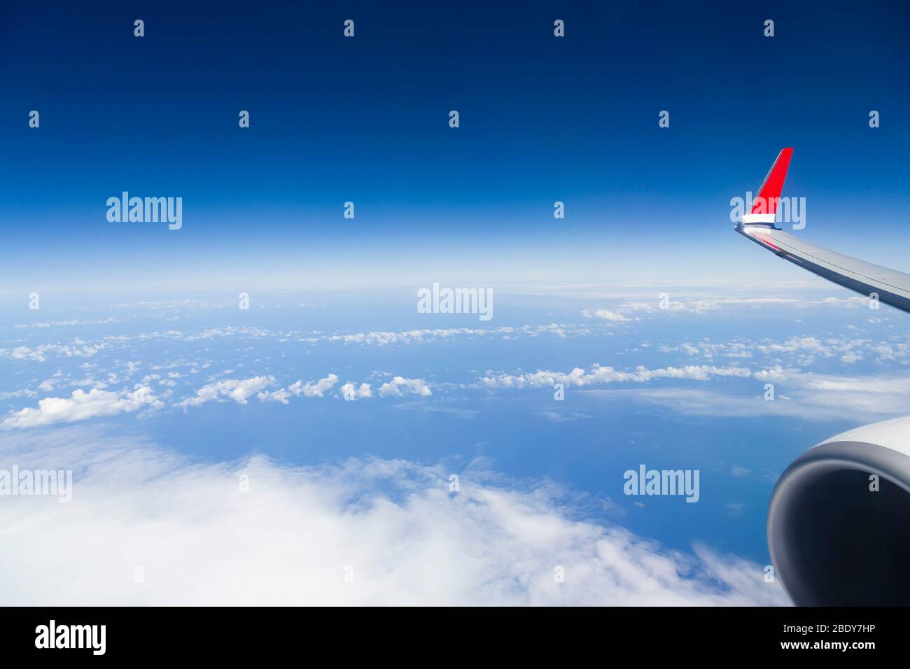 View from window of airliner wing and engine above clouds and Atlantic ocean, with blue sky and horizon. Depicts airline business travel Stock Photo