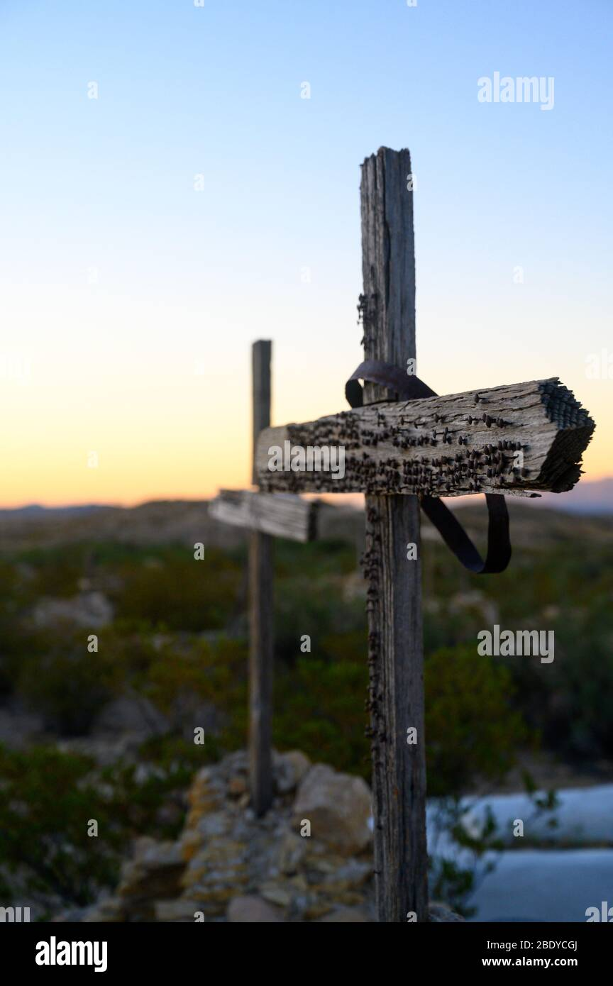 Two wooden crosses with nails in them mark graves in the Terlingua Cemetery in West Texas, where the graves are marked by handmade embellishments. Stock Photo