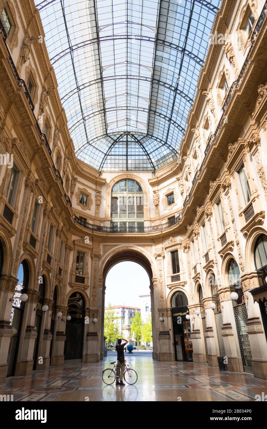 Empty monument: Galleria Vittorio Emanuele II in Milan, Italy during COVID-19 epidemic with man on bicycle shooting photo. Daily life in Milano Italia Stock Photo