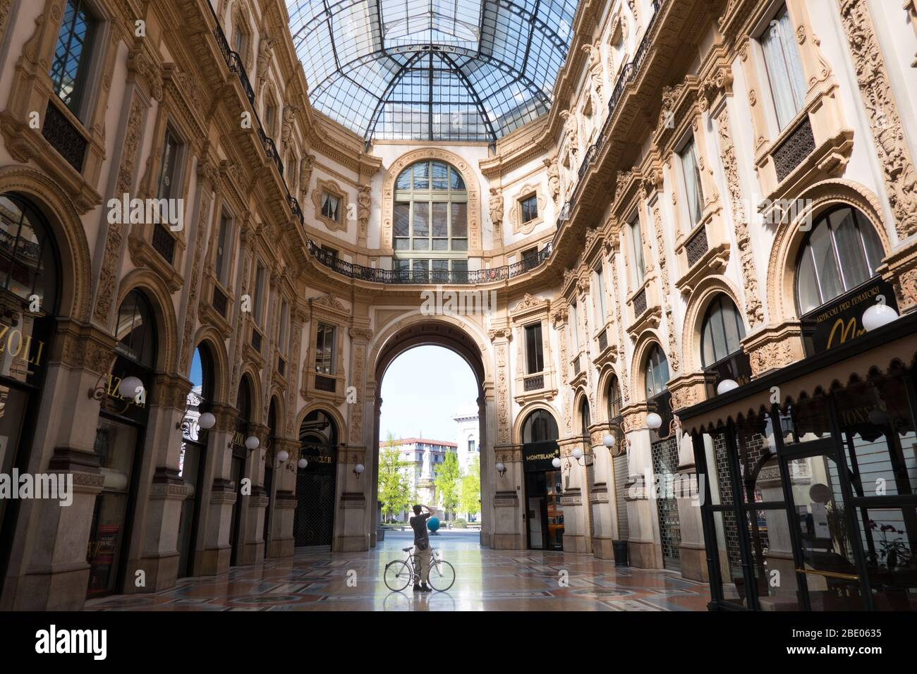 Deserted Galleria Vittorio Emanuele II in Milan, Italy during COVID-19 epidemic with man on bike taking picture. Daily life in Milano with coronavirus Stock Photo