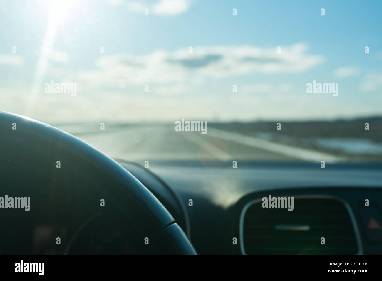View from inside the moving car on the road, Blue sky. transportation concept. Lels flare. Selective focus. Stock Photo