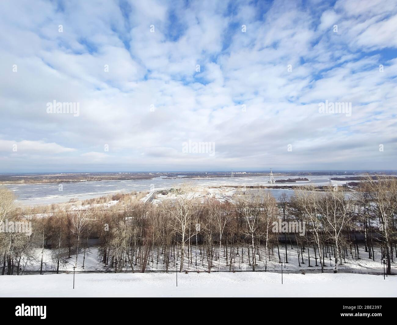 Beautiful early spring river landscape. White clouds over the river and trees on on a sunny day after melting snow. Stock Photo