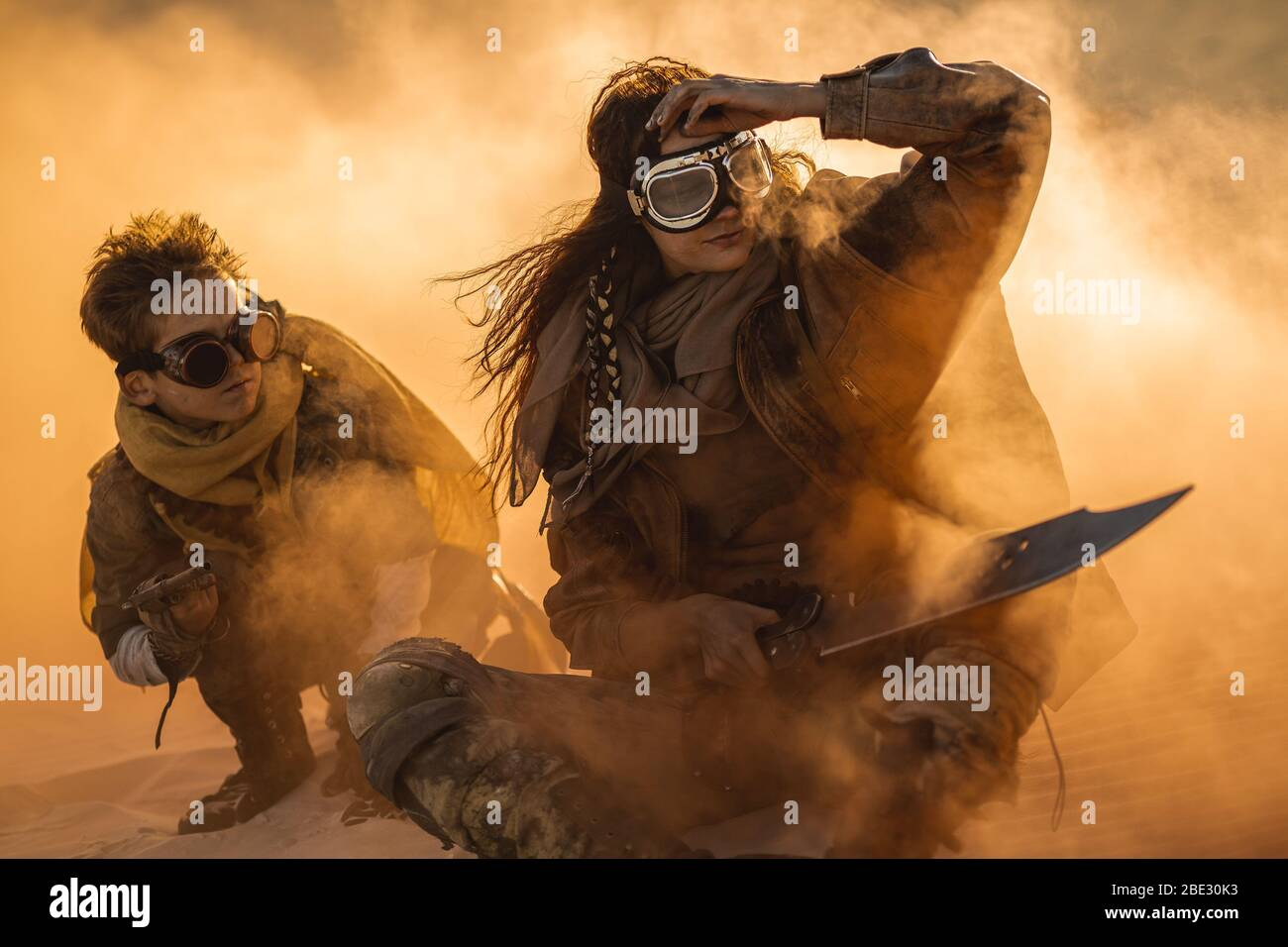 Post apocalyptic woman and boy with weapons outdoors. Desert in smoke and dead wasteland on the background. Aggressive girl warrior in shabby clothes holding sword and young boy with gun and chain sitting in a confident pose. Nuclear post-apocalypse time. Life after doomsday concept.