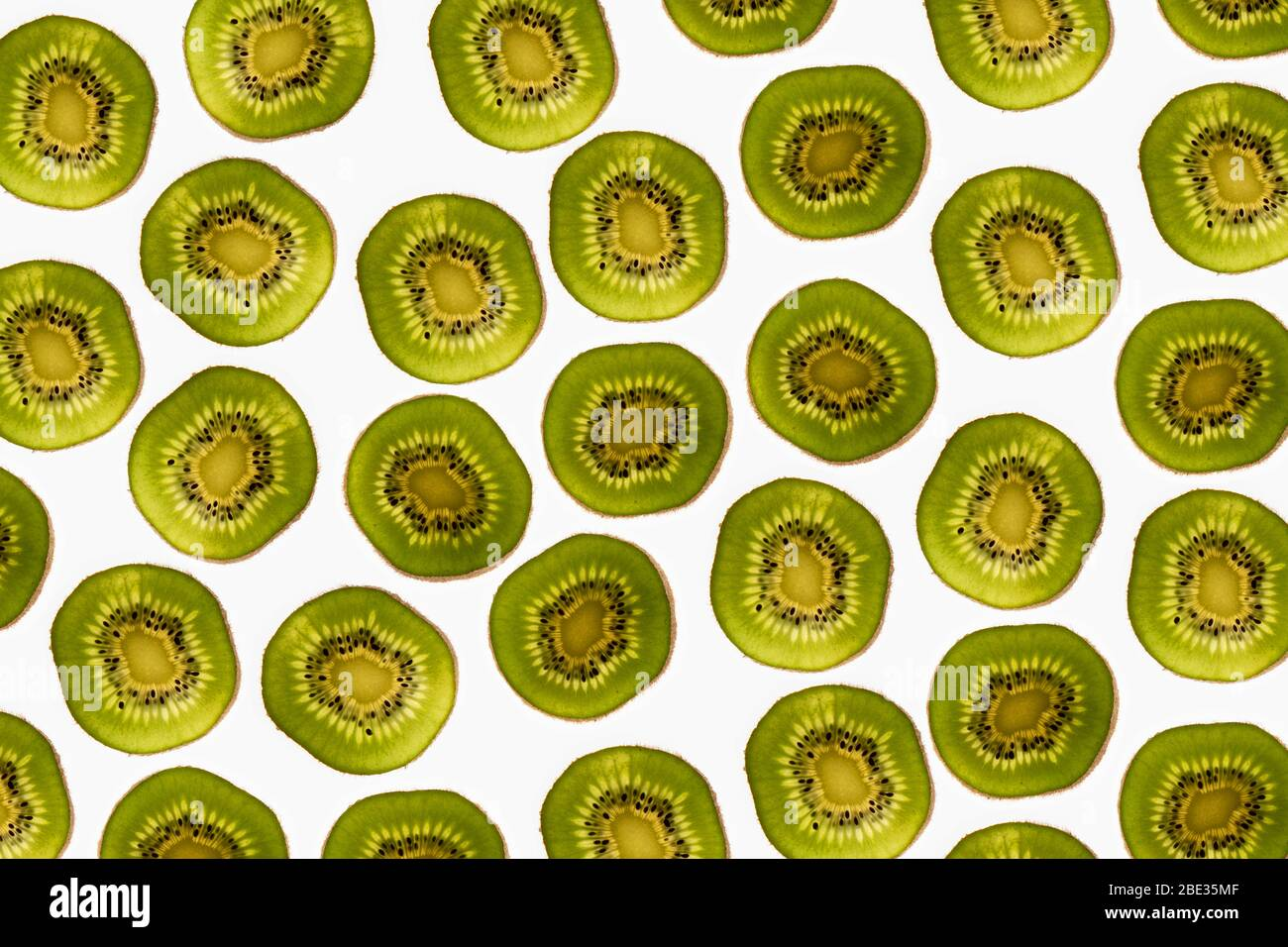 a beautiful image of an interesting pattern of kiwi fruit slices against a bright white background, flatlay Stock Photo