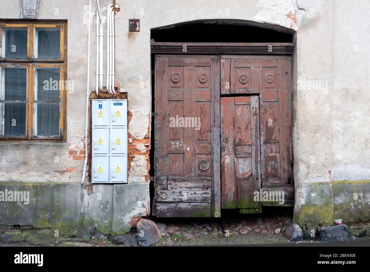 Rough well worn door for apartments with electrical fuse boxes on the side . Tomaszow Mazowiecki Central Poland Stock Photo
