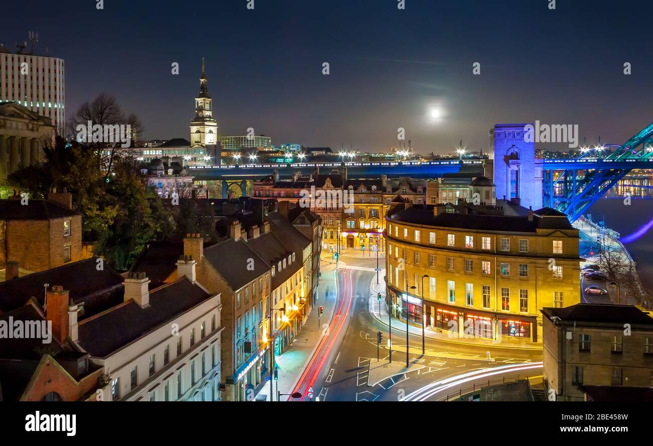 Rooftop Aerial View of Vibrant British City Skyline under Night Sky with Full Moon, Newcastle upon Tyne, UK Stock Photo