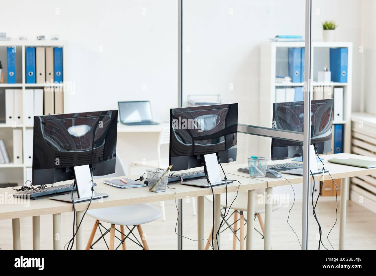 Background Image Of Empty Office Interior With Three Computer Desks In Row Copy Space Stock Photo Alamy