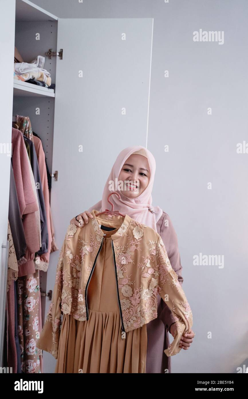 Asian hijab women measure a new gamis by the body in front the