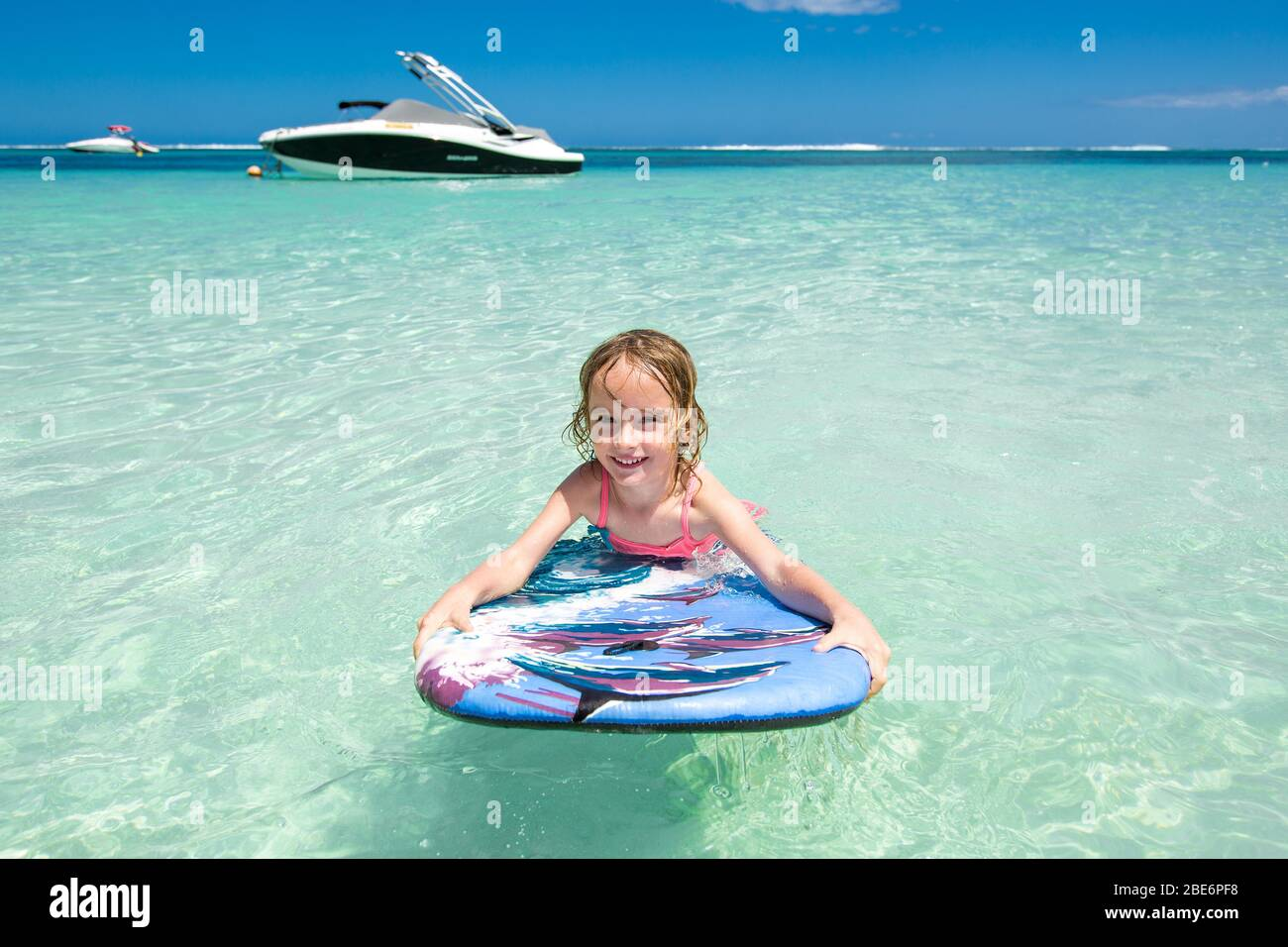 Little baby girl - young surfer with bodyboard has a fun on small ocean waves. Active family lifestyle Stock Photo