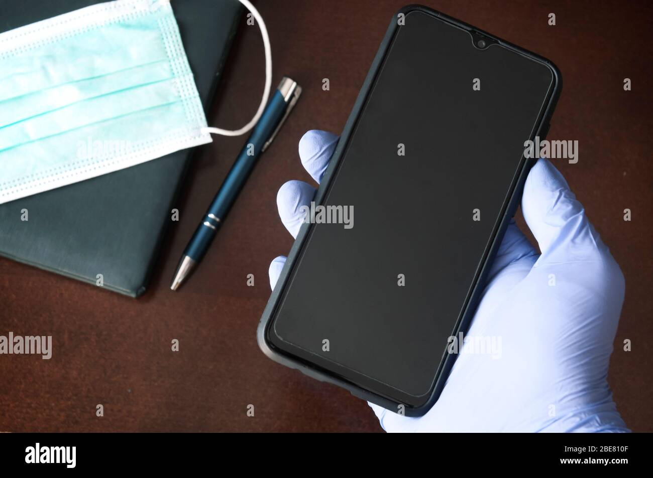 Hand in disposable glove holding mobile phone over a desk- business during pandemics concept Stock Photo