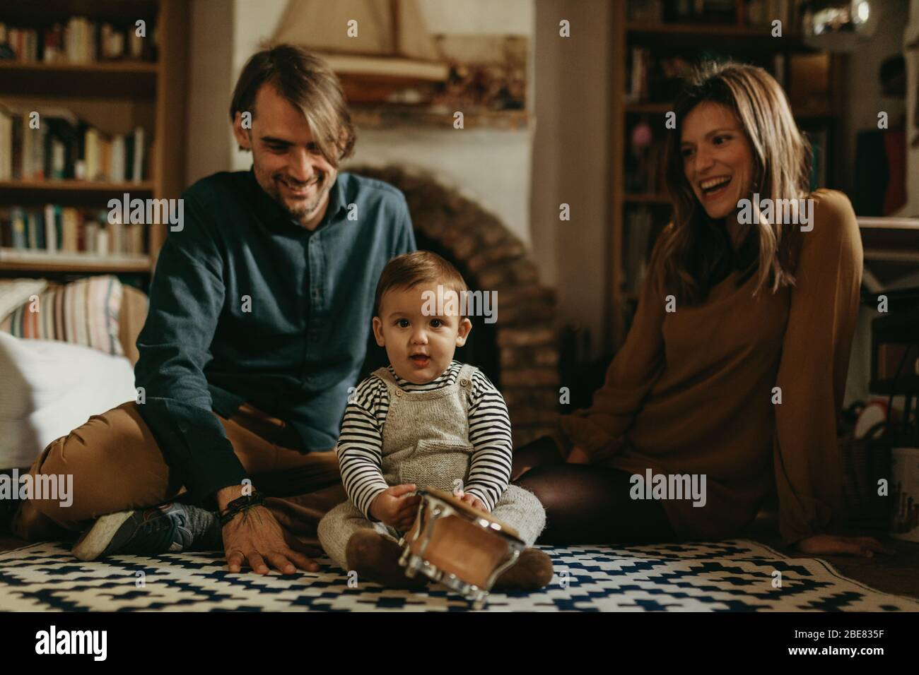 Young happy couple staying at home with their baby son sitting on the living room floor. Stock Photo