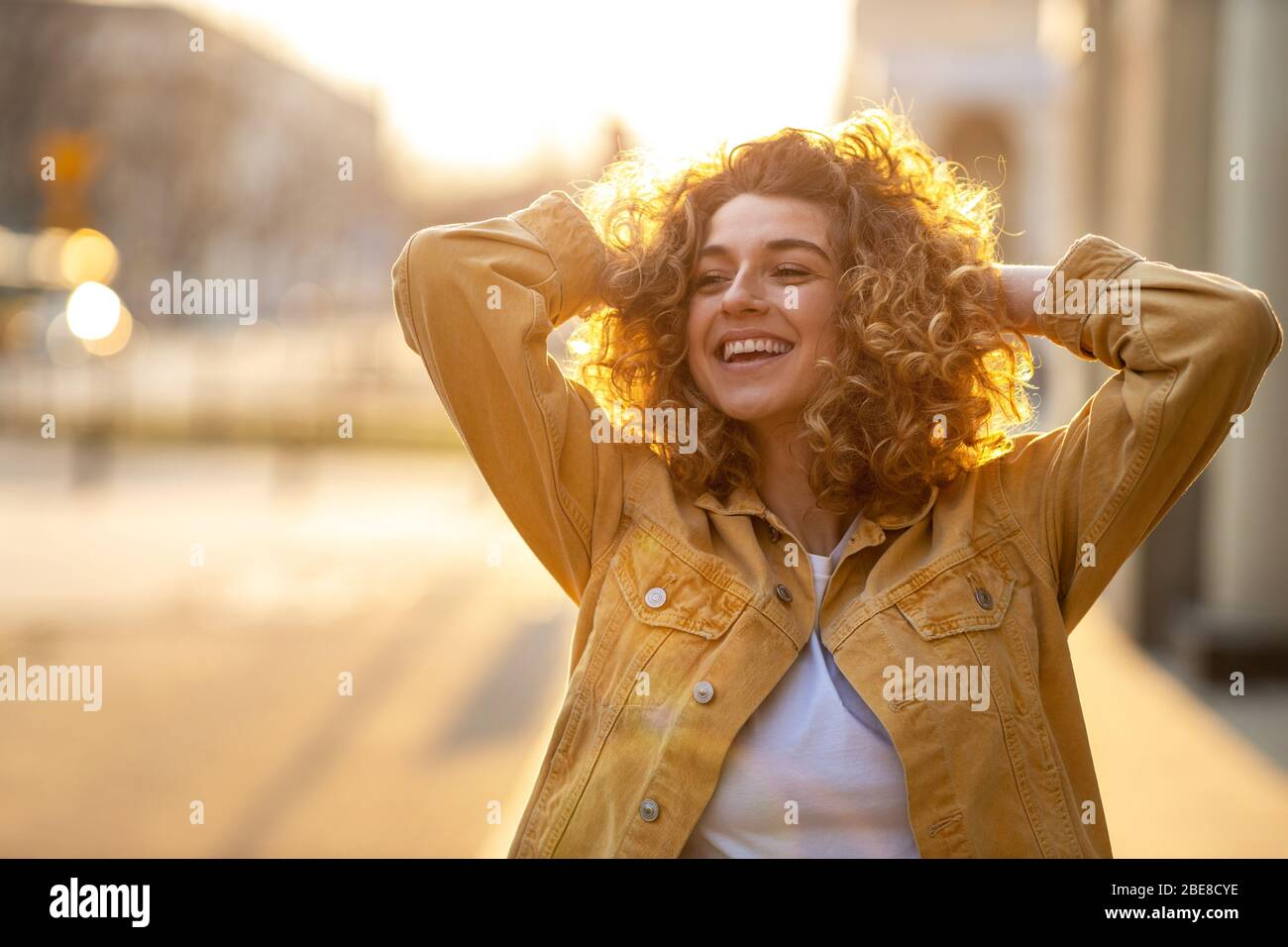 Portrait of young woman with curly hair in the city Stock Photo