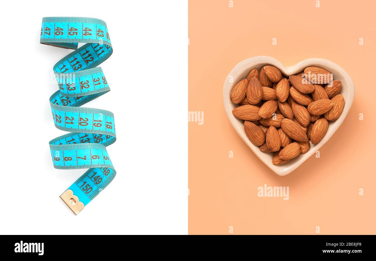 Creative layout of blue centimeter tape on a white background and almond nut in a heart bowl on a pastel pink background. The concept of diet and weig Stock Photo