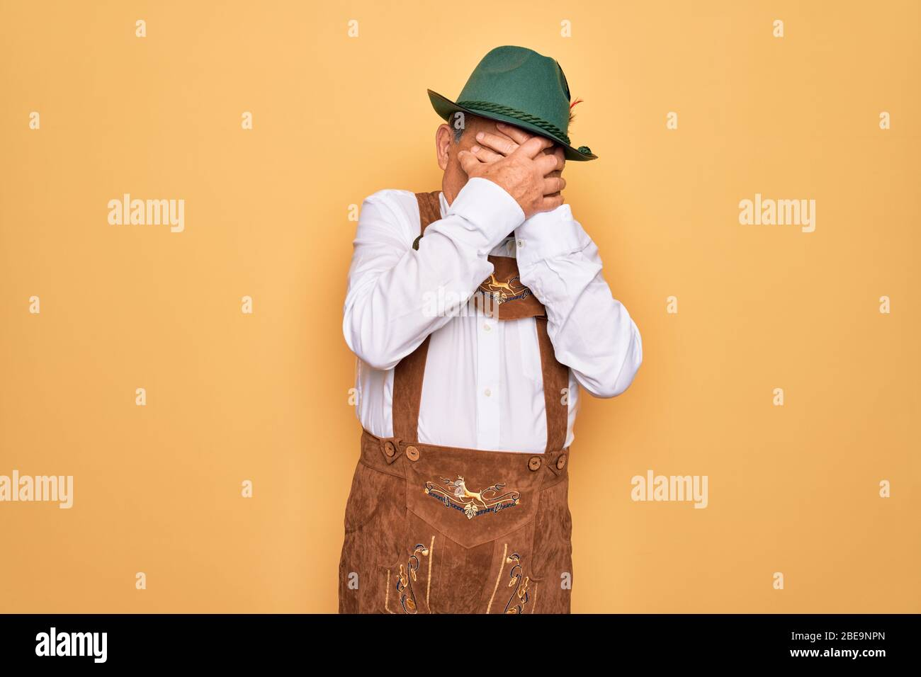 Senior grey-haired man wearing german traditional octoberfest suit over  yellow background with sad expression covering face with hands while  crying. D Stock Photo - Alamy