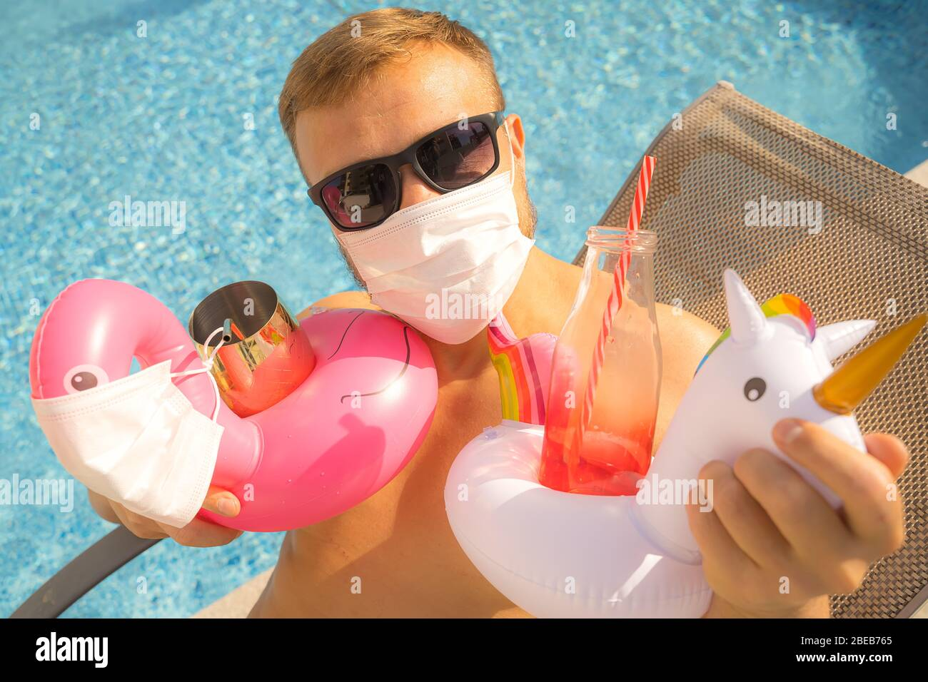 Caucasian male model on a beach chair next to a swimming pool wearing face mask, holding inflatable pool toys Stock Photo
