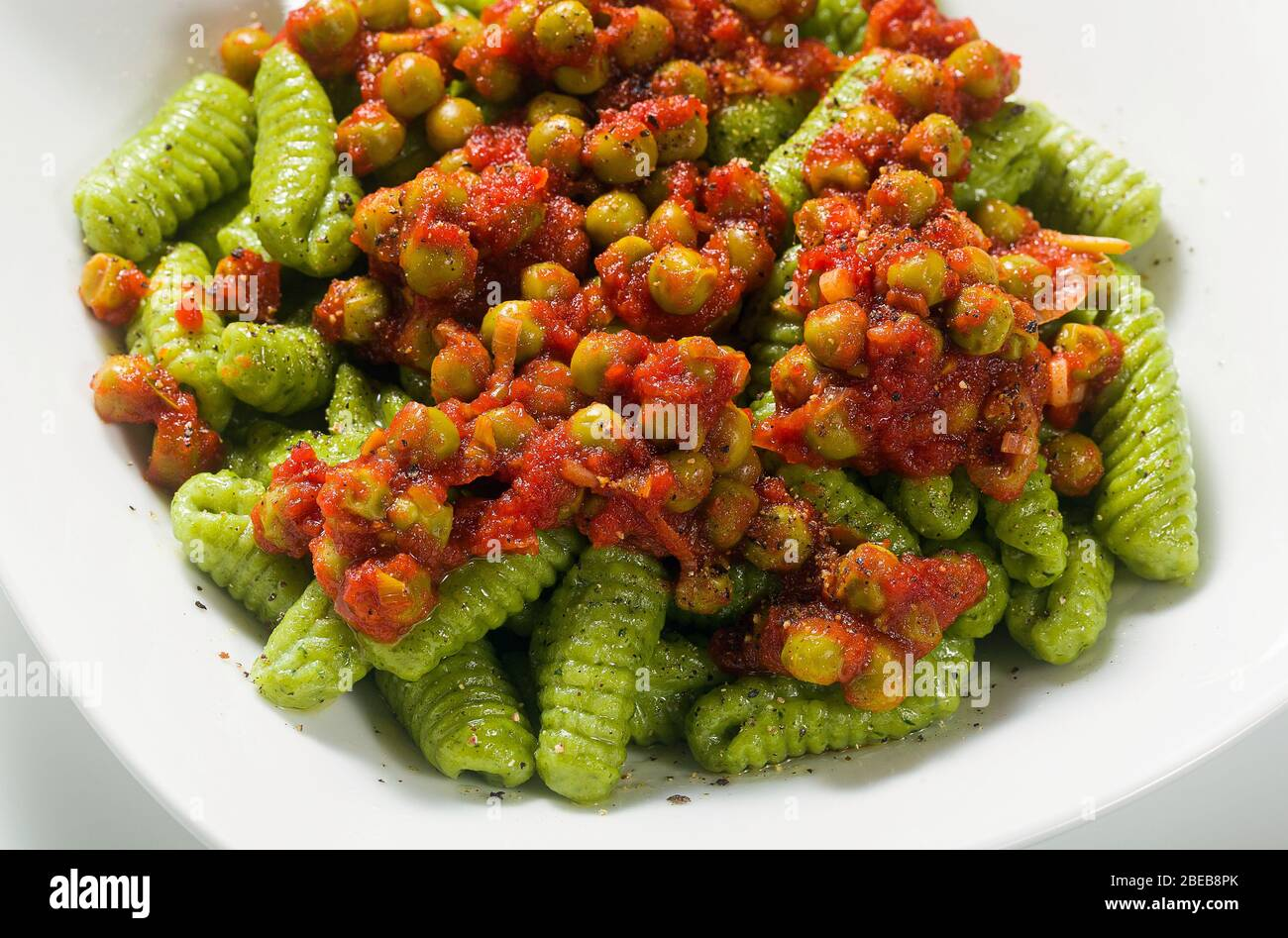 Italian fresh traditional sardinian pasta gnocchi with spinach and green pea tomato sauce. spring pasta for easter holidays. Stock Photo