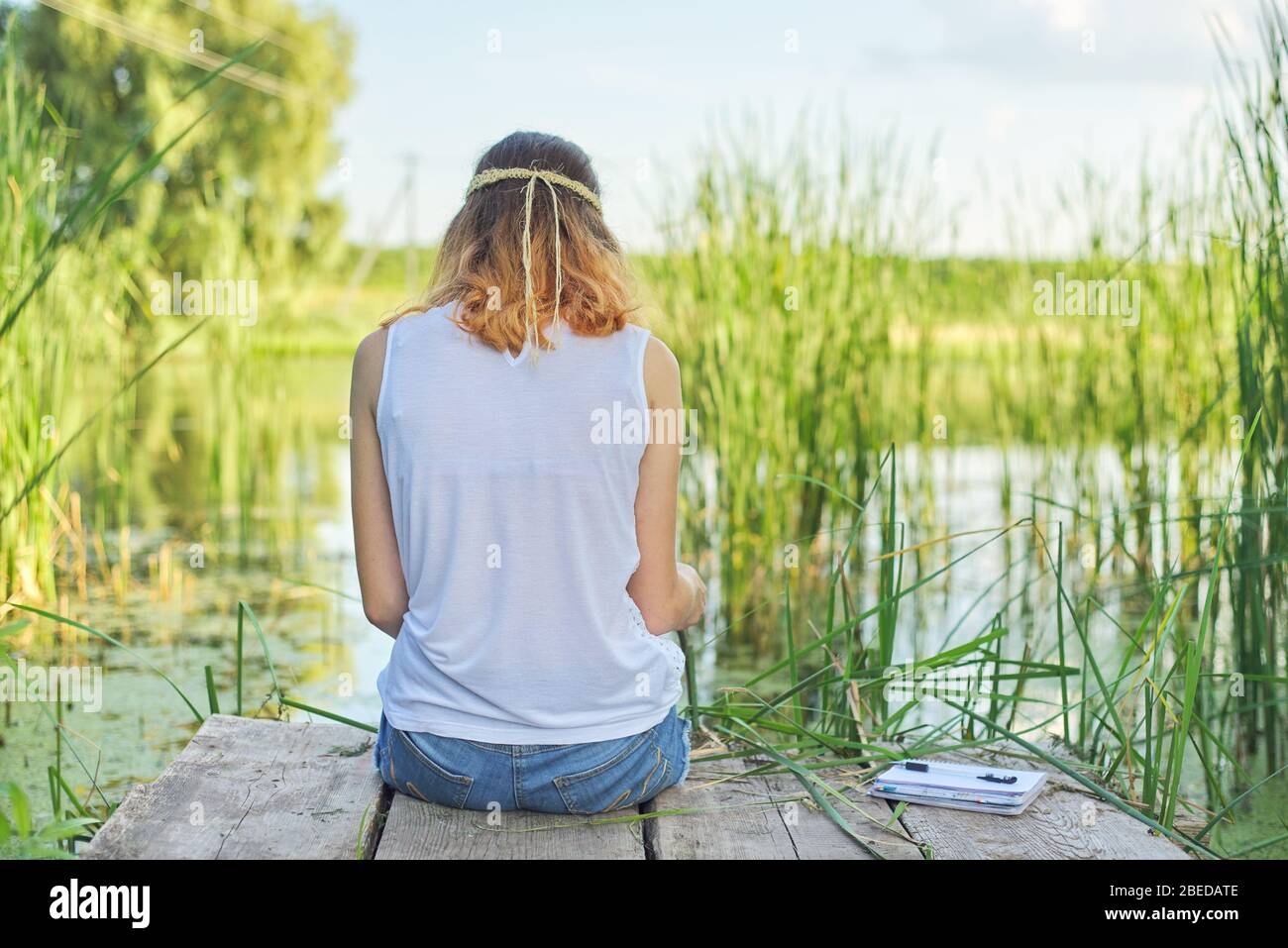 Young woman sitting with her back on wooden pier, enjoying picturesque view of lake water, relaxing in nature on sunny summer day, copy space Stock Photo