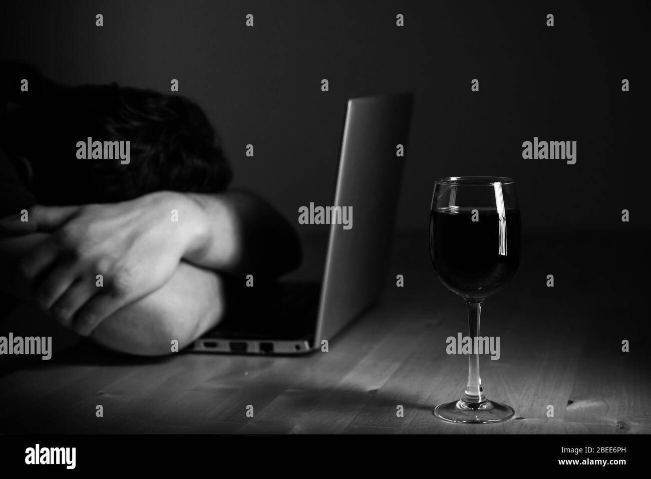 Home office and alcoholism problem - depressed man sitting in front of computer, he hide his face. Wine glass on the table Stock Photo
