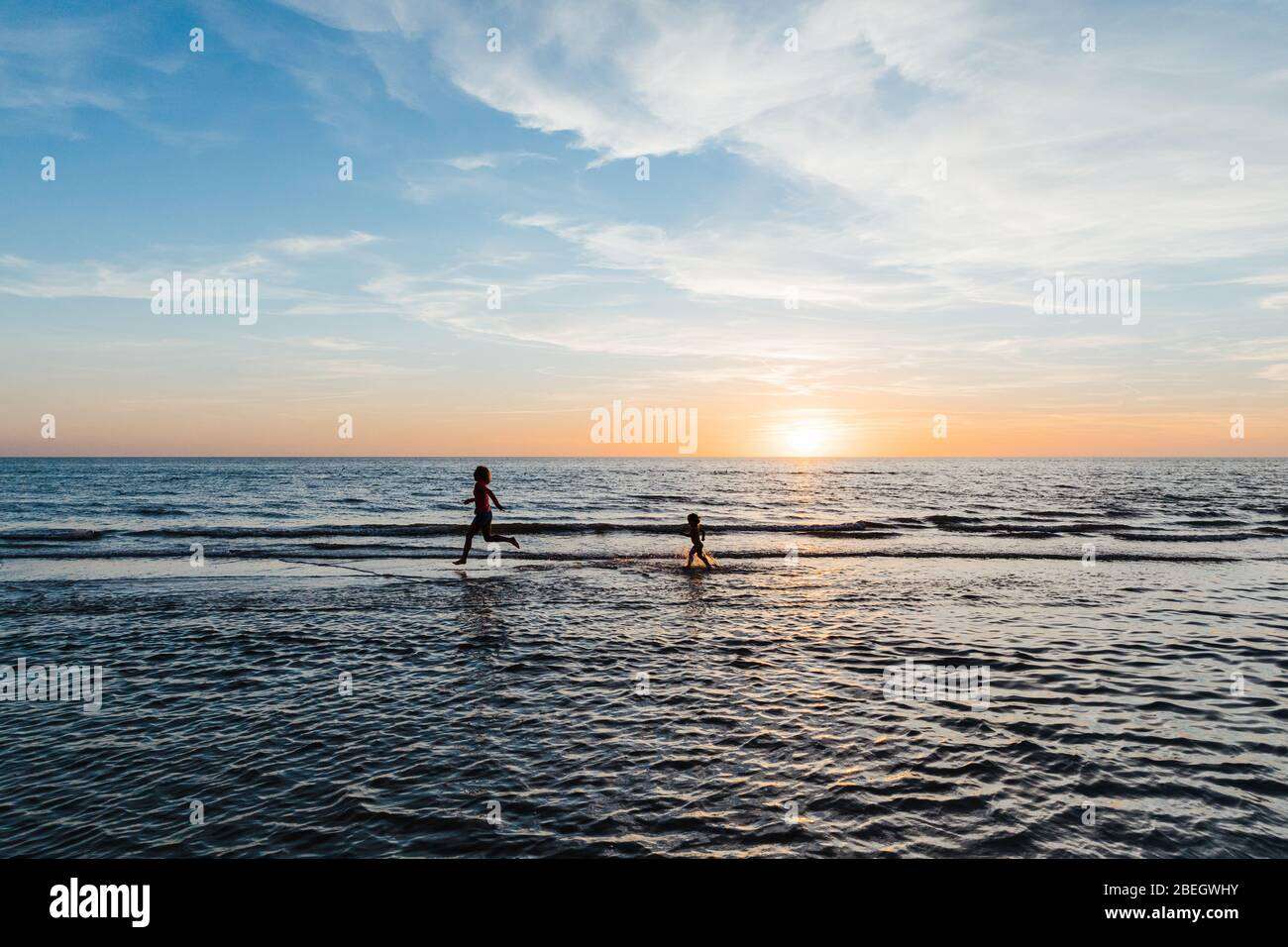 woman and child run in the shallow waters of a florida beach at sunset Stock Photo