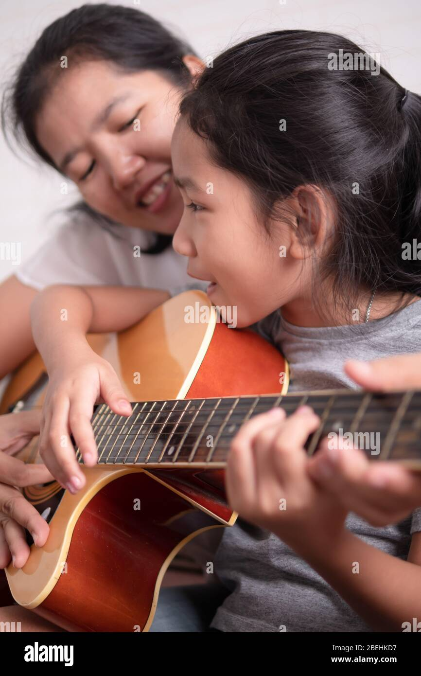 Mom and daughter playing a guitar with happiness on holiday. Asian little girl learning to play music. Children singing and smiling. Select focus shal Stock Photo