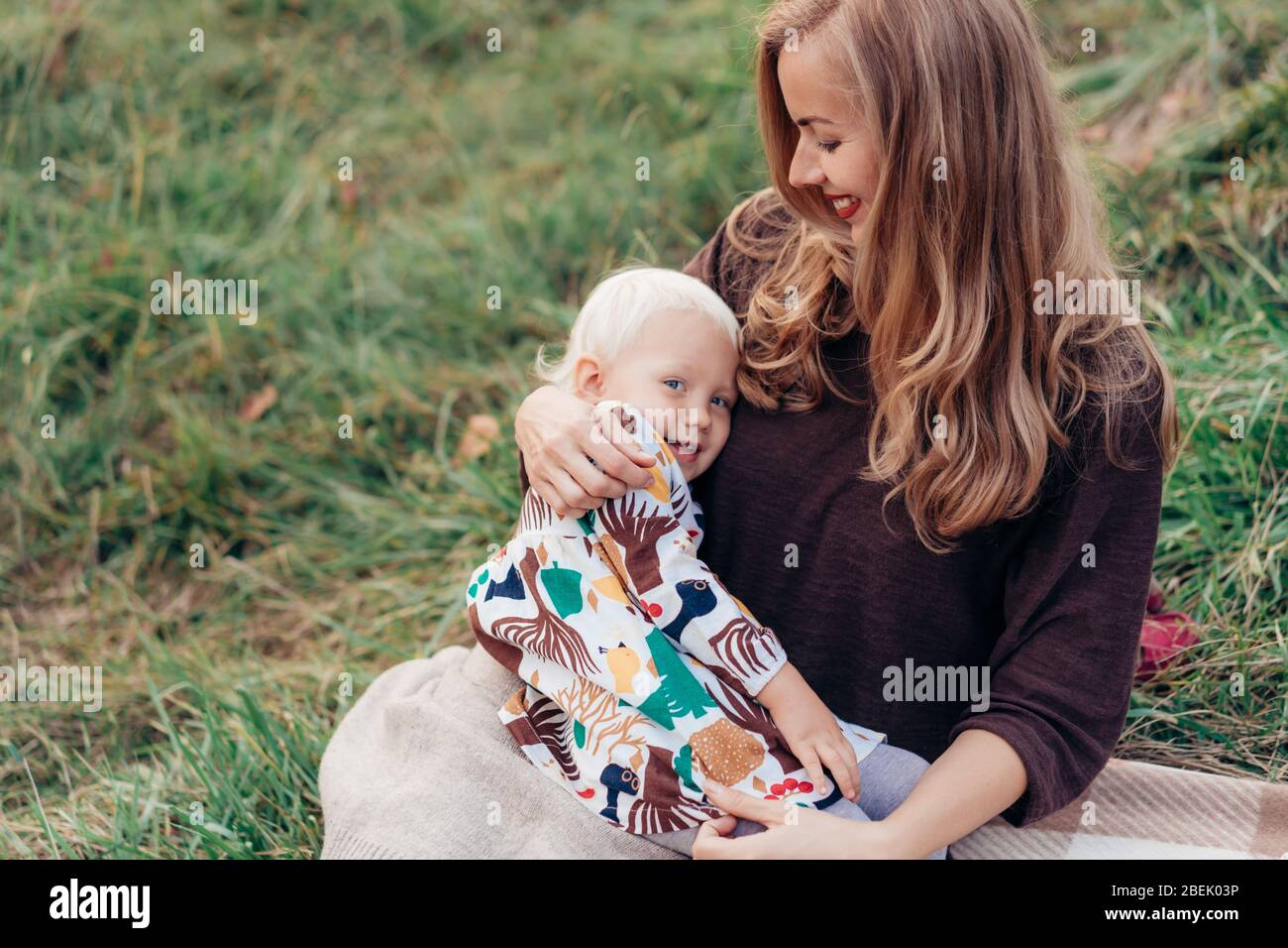 Cute mom hugs and toddler daughters. Family lifestyle in nature. Stock Photo