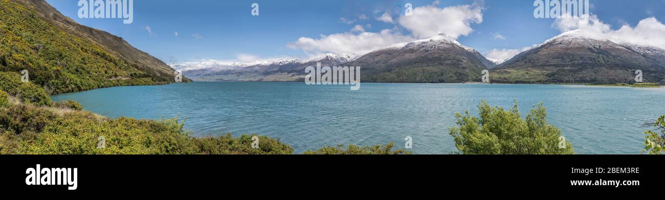 landscape of Wanaka Alpine lake with green shores and snow capped mountains, shot in bright spring light from Boundary creek beach, Otago, South Islan Stock Photo