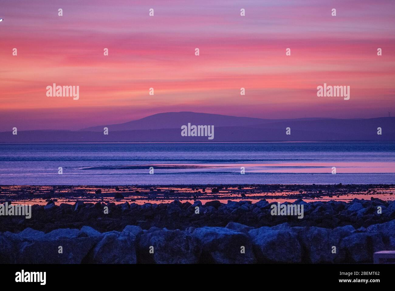 Heysham, Lancashire, United Kingdom. 14th Apr, 2020. Spectacular after glow behind the South Lakeland Fells, across Morecambe Bay brings to a close Tuesday. Credit: Photographing_North/Alamy Live News Stock Photo