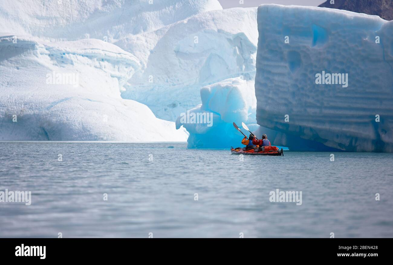 2 men traveling with a sea kayak in Eastern Greenland Stock Photo