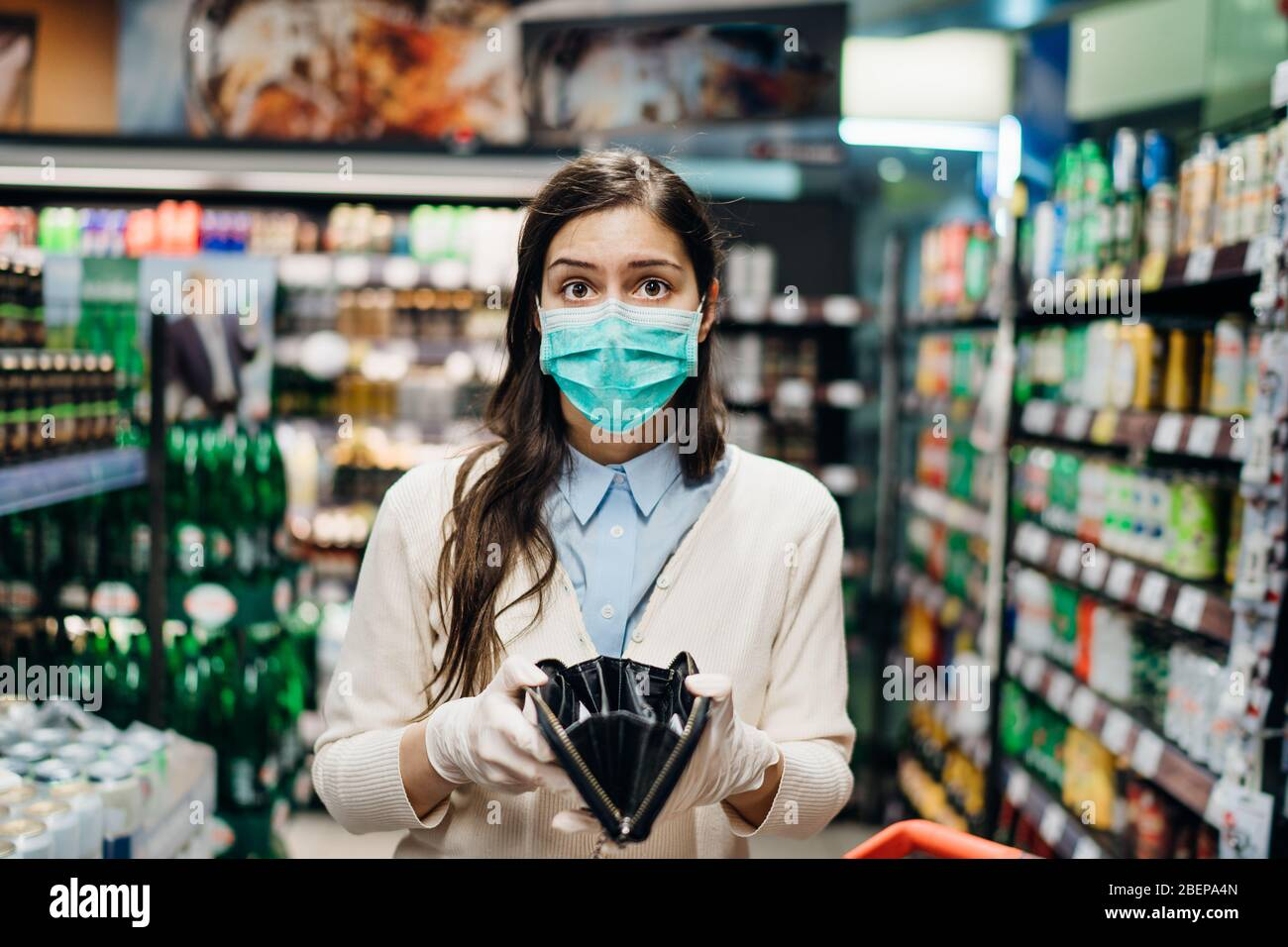 Stressed woman with mask shopping in grocery store with an empty wallet.Bankruptcy/recession.Covid-19 quarantine lockdown impact.Unemployed person in Stock Photo