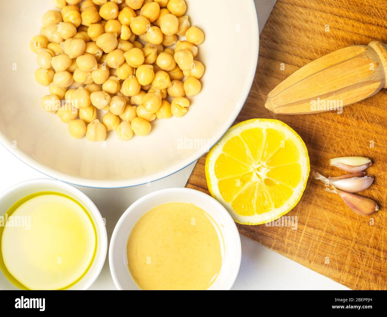 Bowls of chick peas olive oil and tahini with garlic cloves half a lemon and a lemon squeezer for making hummus Stock Photo
