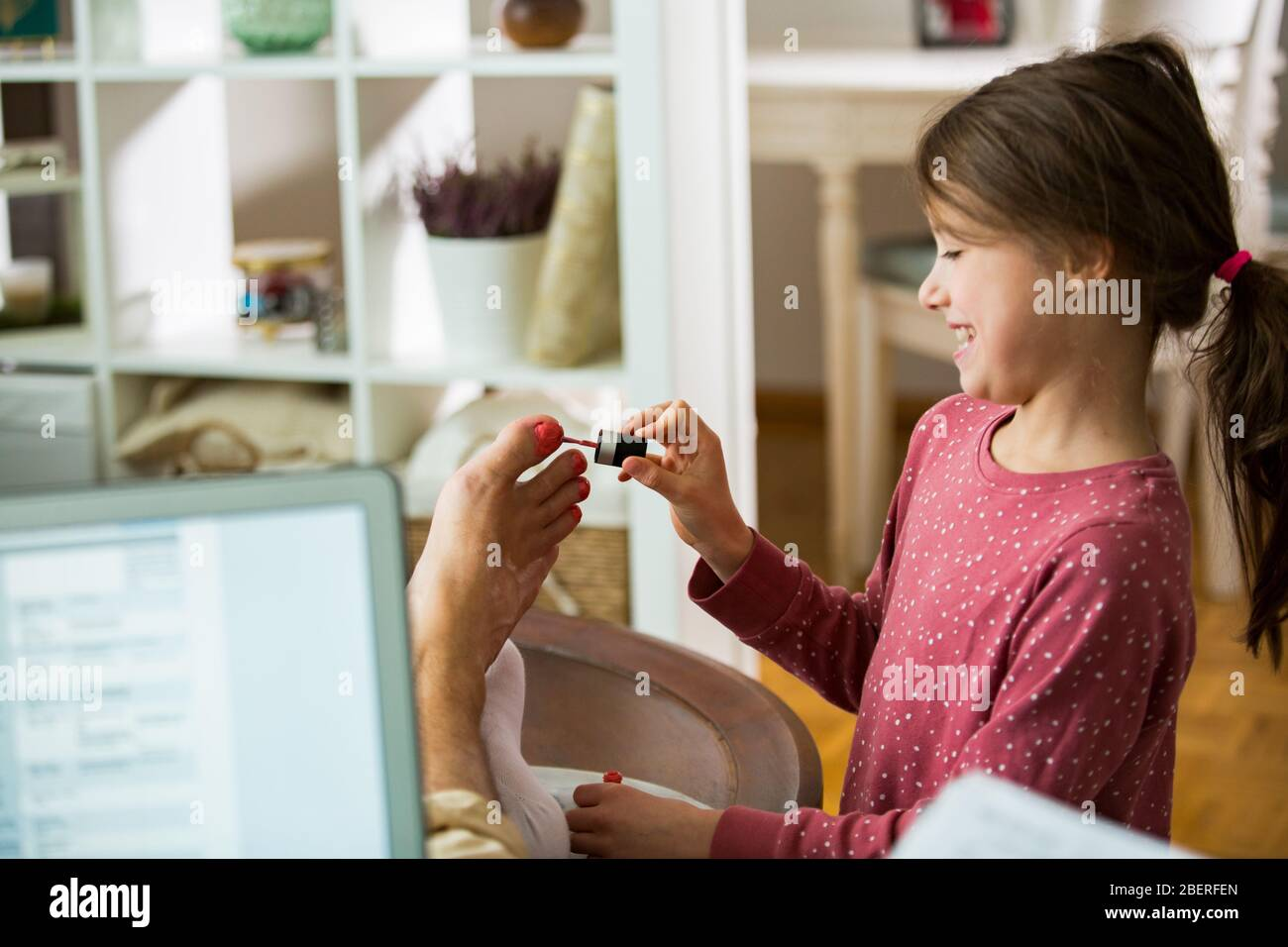 Child playing and disturbing father working remotely from home. Little girl applying nail polish on toenails. Man sitting on couch with laptop. Family Stock Photo