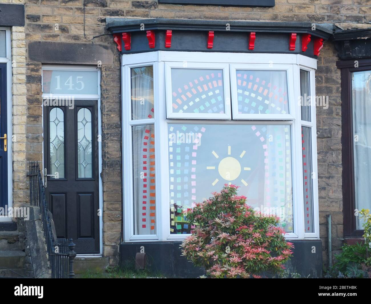 Display of cut coloured paper forming the symbol of a rainbow and sunshine as message of hope during the Coronavirus crisis in bay window of UK house Stock Photo