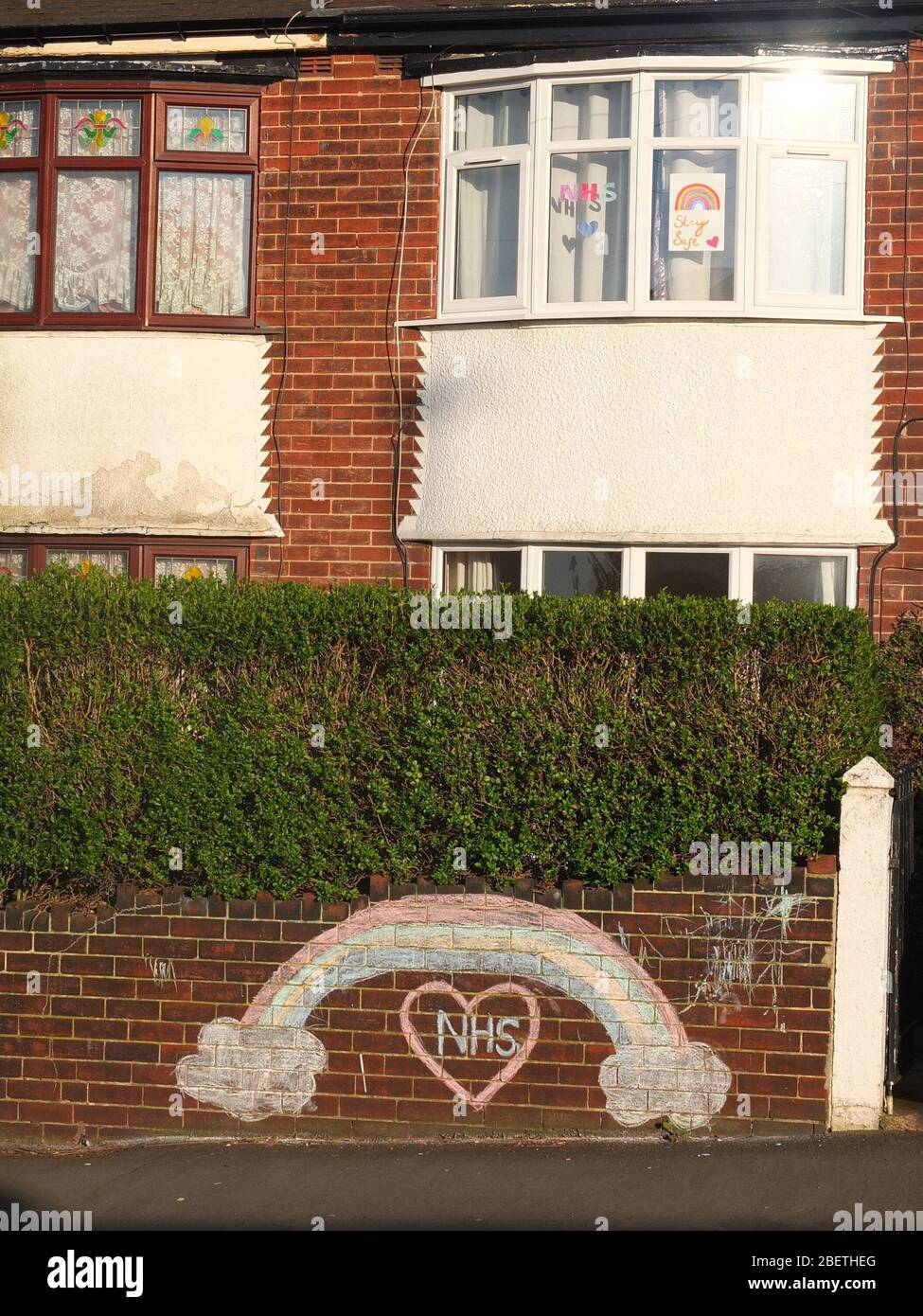 A chalked rainbow and message of support and gratitude to the NHS on the front wall of a house in Sheffield UK also with rainbows in upstairs window. Stock Photo