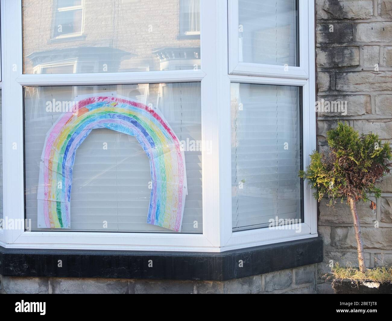 A colourful child's drawing of a rainbow in a house window during the UK Coronavirus Crisis and Lockdown signifying a message of hope for the future Stock Photo