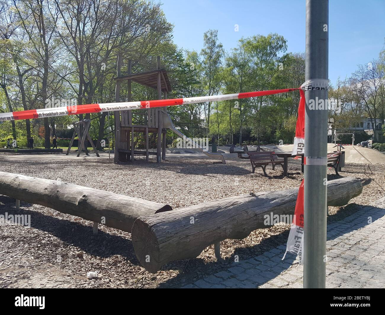 Empty , abandoned children playground or play field in park or forest with slide closed with police barrier warning tape due to corona virus covid-19 Stock Photo