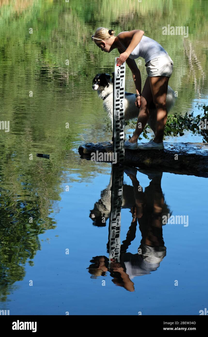 GIRL WITH DOG MIRRORED IN THE RIVER Stock Photo
