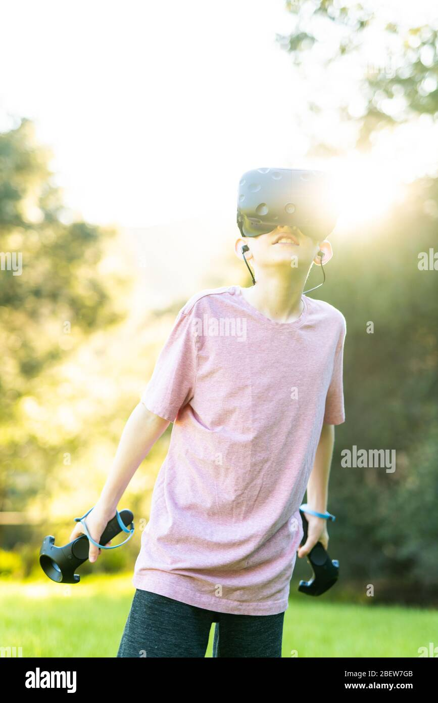 Tween having virtual experience with VR goggles outside in green field Stock Photo